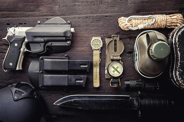 Equipamento tático militar para a partida. variedade de equipamento de caminhadas de sobrevivência em fundo de madeira