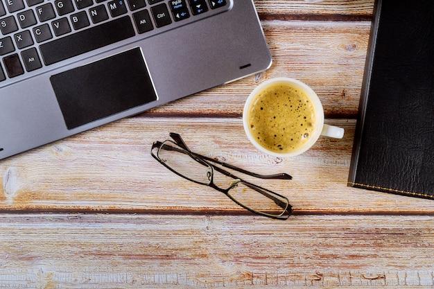 Equipamento trabalhando no escritório em copos de laptop na xícara de café expresso