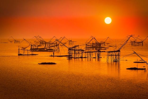 Equipamento tradicional de rede quadrada ao nascer do sol no canal pakpra, phatthalung, tailândia