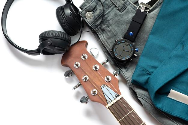 Equipamentos casuais dos homens para a roupa do homem com a guitarra, as calças de brim, o relógio, o fone de ouvido e a camisa isolados no fundo branco, vista superior.