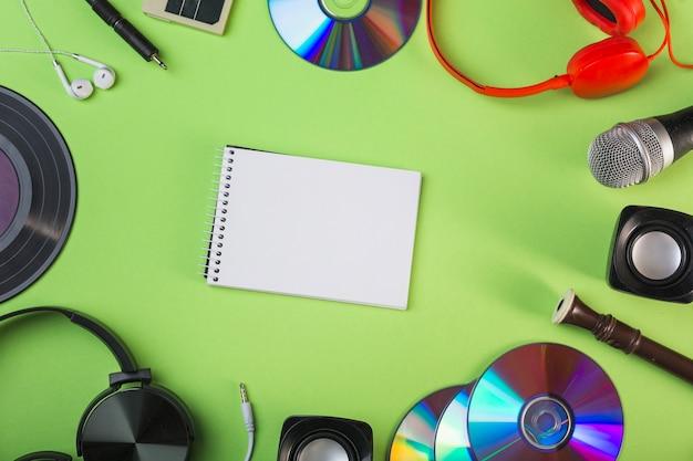 Equipamentos de áudio em torno do bloco de notas espiral em branco sobre fundo verde