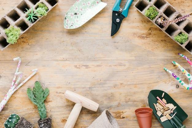 Equipamentos de jardinagem e bandeja de turfa; pote de plástico no cenário de madeira