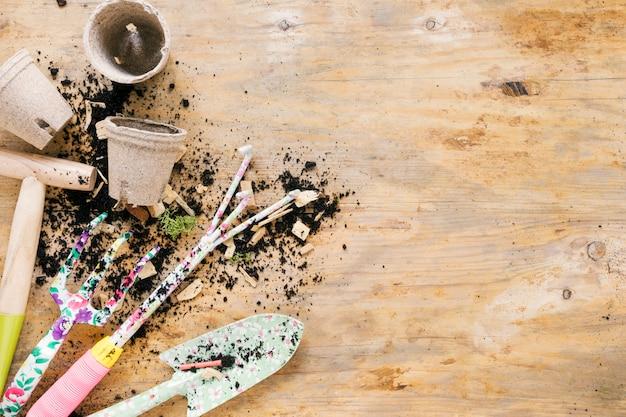 Equipamentos de jardinagem e solo com pote de turfa em branco na mesa