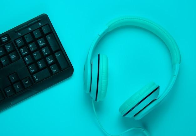 Equipamentos de jogo. teclado e fone de ouvido em luz neon azul