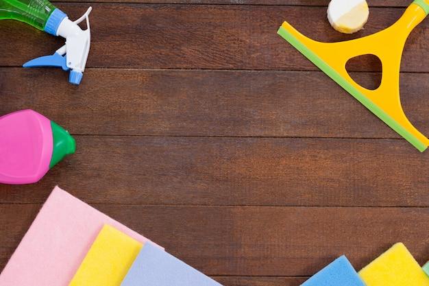 Equipamentos de limpeza, dispostos no fundo do piso de madeira