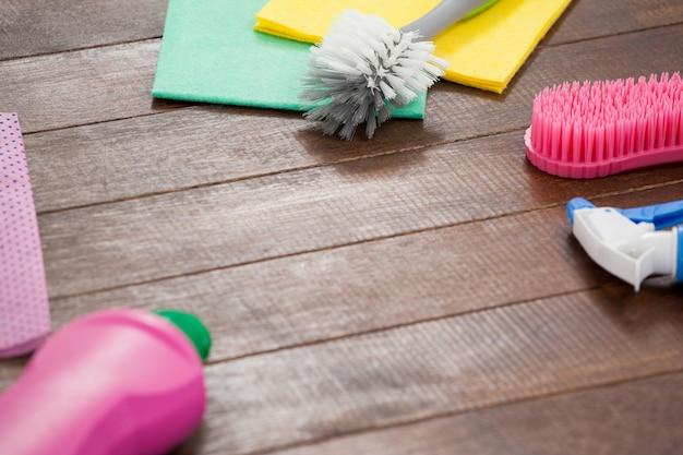 Equipamentos de limpeza dispostos no piso de madeira