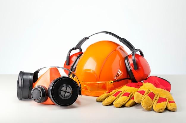 Equipamentos de proteção individual, respiratório, capacete, fones de ouvido, óculos e luva em superfície cinza.