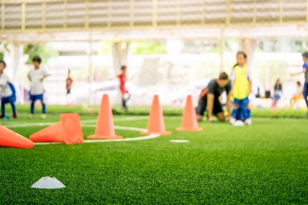 Equipamentos de treinamento de futebol no campo de treinamento com crianças