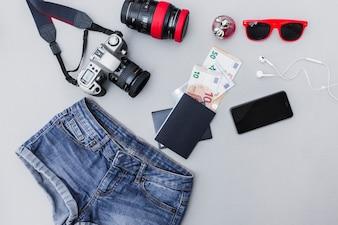 Equipamentos de viagem com roupas em fundo cinza