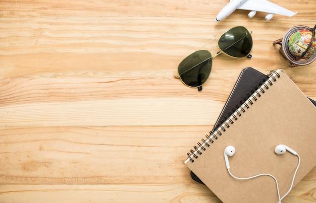 Equipamentos de viagem do mundo, como óculos de sol, cadernos, mapas.