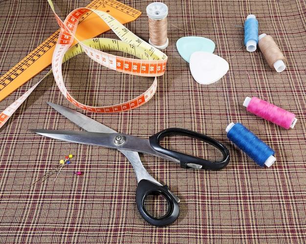 Equipamentos e ferramentas sob medida, incluindo fita, giz, linha, tesoura e um pedaço de tecido de lã.
