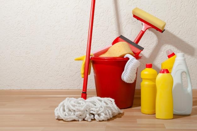 Equipamentos e suprimentos de limpeza doméstica em um balde no chão