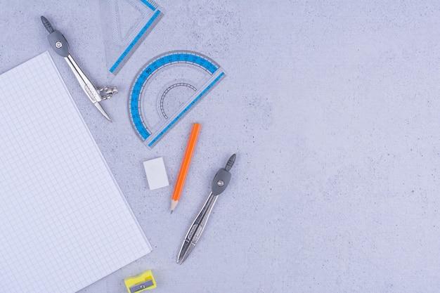 Equipamentos escolares e de escritório isolados na superfície cinza