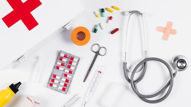 Equipamentos médicos com caixa de primeiros socorros em fundo branco