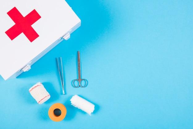 Equipamentos médicos com kit de primeiros socorros em fundo azul