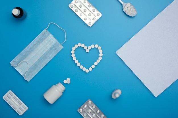 Equipamentos médicos, incluindo uma máscara, uma pílula, um frasco de comprimidos, uma colher com os comprimidos.