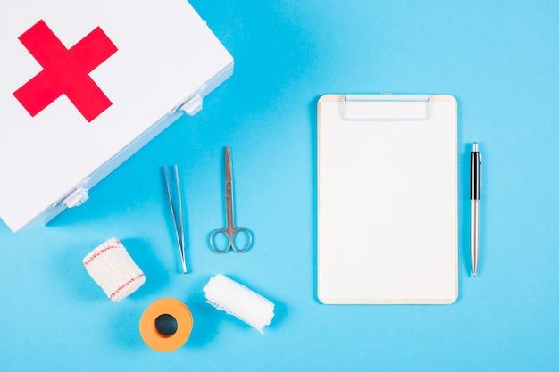 Equipamentos médicos; kit de primeiros socorros; prancheta e caneta sobre fundo azul