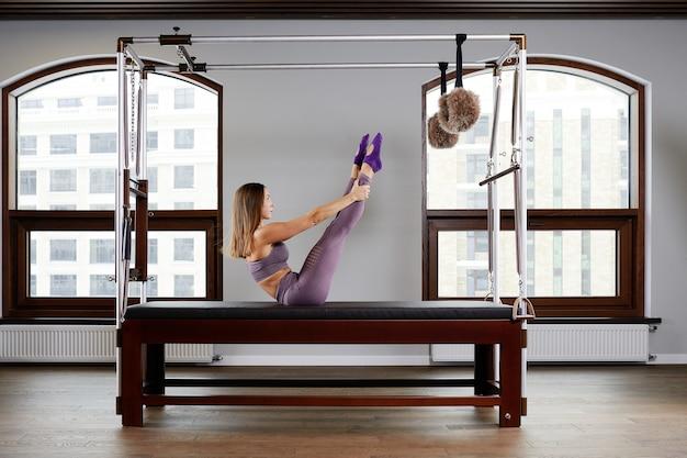 Equipamentos modernos reformador cadilac para pilates na academia, conceito de saúde e reabilitação, instrutor realiza exercícios no reformador para correção do sistema musculoesquelético.
