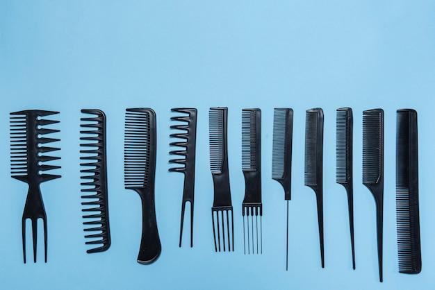 Equipamentos para modelagem e corte de cabelo, como pentes e tesouras dispostos em um fundo azul