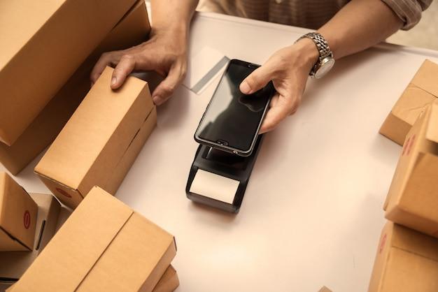 Equipe a mão que guarda a máquina do dinheiro do tecnology do nfc do leitor de cartão do crédito.