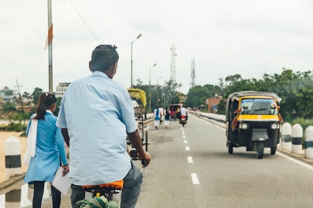 Equipe a montada de uma bicicleta e os povos que andam na estrada com os carros que correm perto do templo de mahabodhi em bodh gaya, bihar, índia.