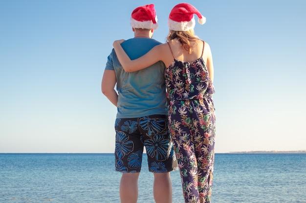 Equipe a mulher de aperto em chapéus do natal e a vista da praia do mar.