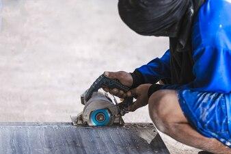 Equipe a telha profissional do corte do trabalhador com interior bonde da construção da serra circular.