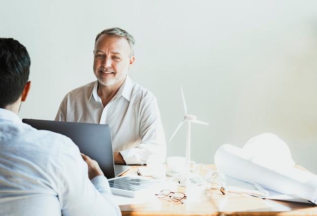 Equipe alegre de engenheiros ecológicos em uma reunião