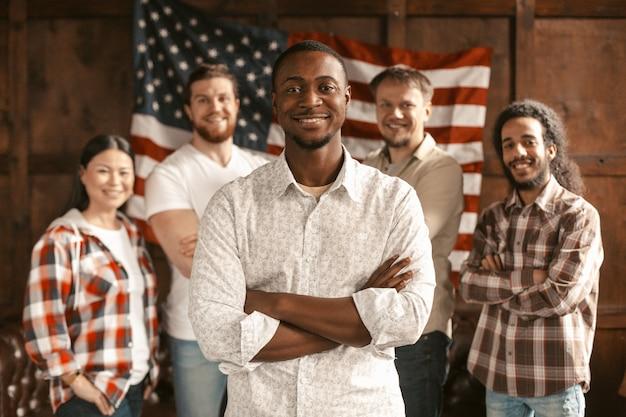 Equipe americana diversificada em pé com a bandeira da américa