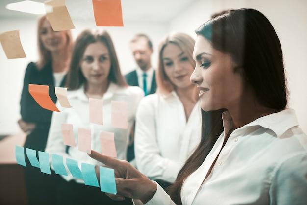 Equipe amigável, empresários discutindo juntos olhando adesivos coloridos na porta do escritório