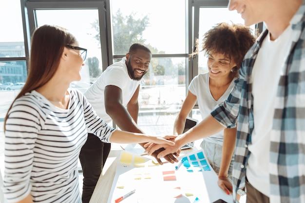 Equipe amigável. jovens colegas positivos de mãos dadas e desfrutando de uma atmosfera amigável enquanto trabalham juntos no escritório