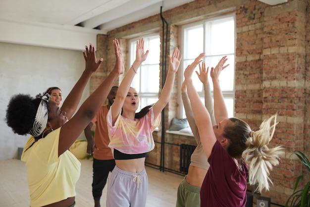 Equipe animada de dançarinos apoiando uns aos outros durante o treinamento esportivo no clube de saúde