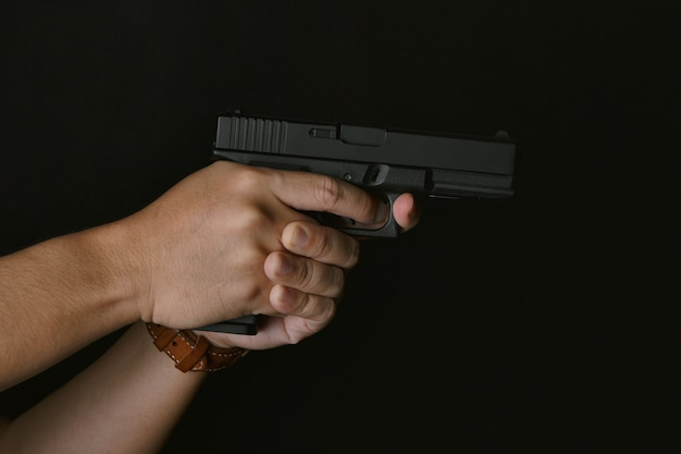 Equipe apontar a arma pronta para disparar, assassino com a pistola do revólver de 9mm que espera roubando o conceito do crime da vítima, da arma e da violência.