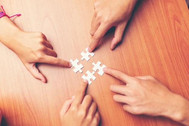 Equipe as mãos que conectam a parte do enigma dos pares no escritório. negócio, sucedido