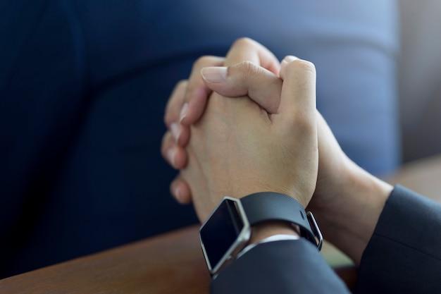 Equipe as mãos que rezam em uma bíblia sagrada na igreja para o conceito da fé, a espiritualidade e a religião cristã.