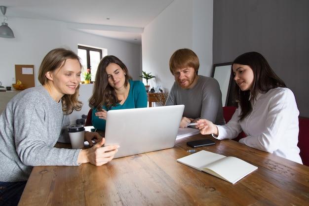 Equipe assistindo apresentação na mesa de reunião