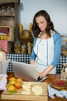 Equipe atenciosa usando laptop no balcão da padaria