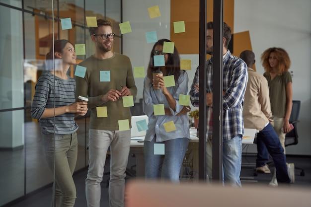 Equipe bem-sucedida de colegas de trabalho executivos felizes olhando para notas adesivas em um quadro de vidro
