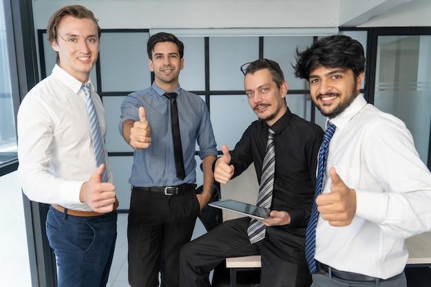 Equipe bem sucedida de sorriso do negócio que mostra o polegar acima.