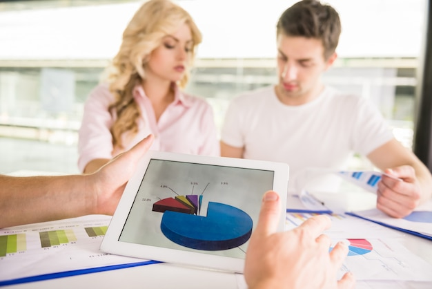 Equipe bem sucedida nova que senta-se na tabela no escritório.