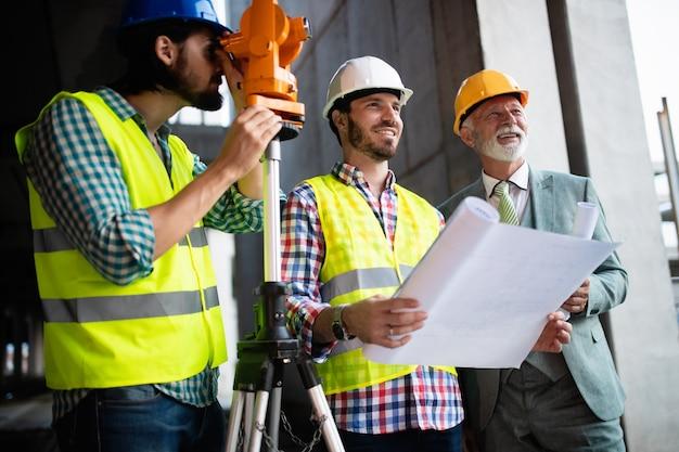 Equipe confiante de arquitetos e engenheiros trabalhando juntos em um canteiro de obras moderno