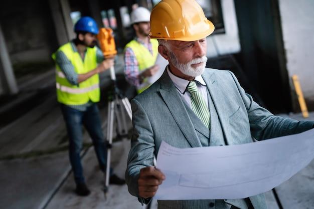 Equipe confiante de arquitetos e engenheiros trabalhando juntos no canteiro de obras