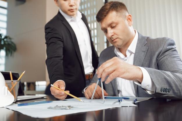 Equipe confiante de engenheiros trabalhando juntos em um estúdio de arquiteto.