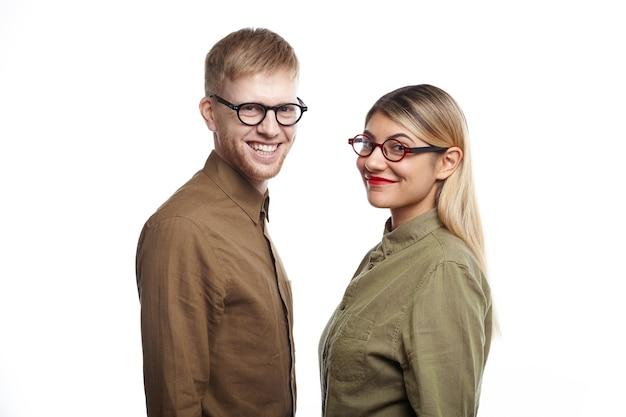 Equipe confiante e bem-sucedida de dois jovens ambiciosos parceiros de negócios, masculino e feminino, posando para uma parede branca e olhando com sorrisos alegres, felizes com os bons resultados de seu projeto comum