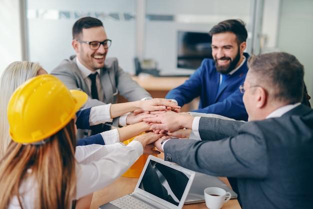 Equipe corporativa que empilha as mãos ao sentar-se na mesa na sala de reuniões. substitua o medo do desconhecido por curiosidade.