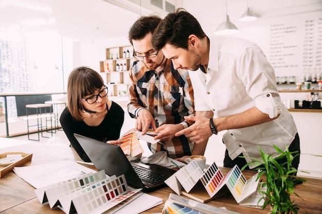 Equipe criativa de designers gráficos trabalhando em um novo projeto usando amostras de cores e desenhos