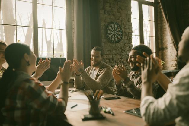Equipe criativa de freelancers aplaudindo juntos
