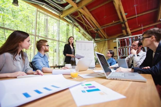 Equipe criativa. designer gráfico feminino discutindo com colegas de trabalho no escritório.