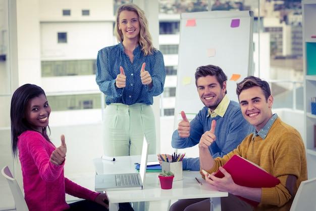 Equipe criativa do negócio dando polegares para cima