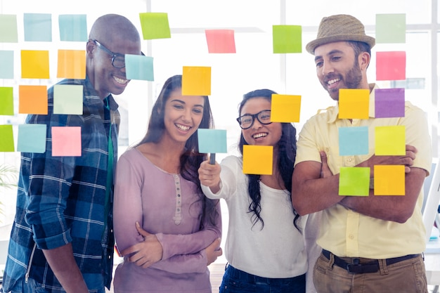 Equipe criativa feliz discutindo sobre notas adesivas no vidro no escritório